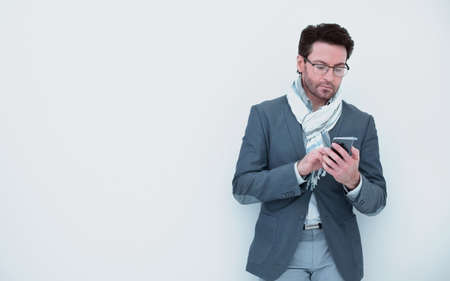 businessman with scarf on neck typing SMS on smartphone. Stock Photo