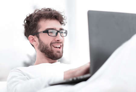 handsome man working on laptop lying on bed Stock Photo