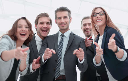 A group of business people standing and pointing at you