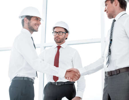 Two architects shaking hands after a meeting in office