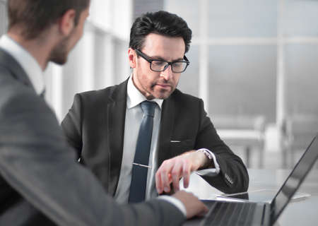 two businessmen discussing information from a laptop. Stock Photo