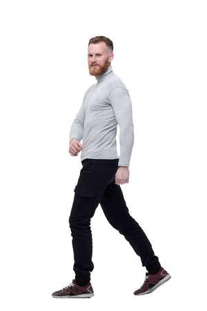 charismatic bearded man walks forward . isolated on white background Stock Photo