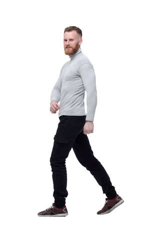 El carismático hombre barbudo camina hacia adelante. aislado sobre fondo blanco Foto de archivo