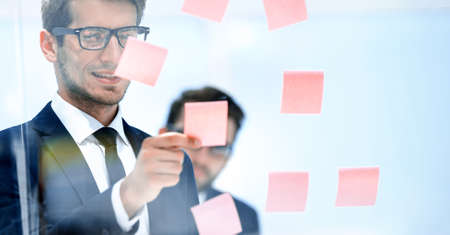serious employee reads a sticker-note on the office Board.