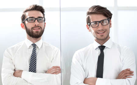 Two happy confident young businessmen standing with arms crossed in office Stock Photo