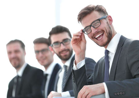 close up.smiling businessman sitting on the background of colleagues