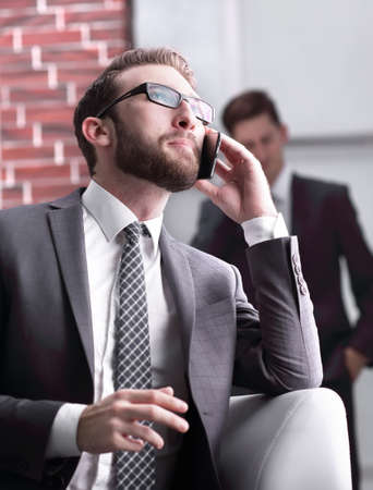 Handsome businessman speaking on mobile phone in office