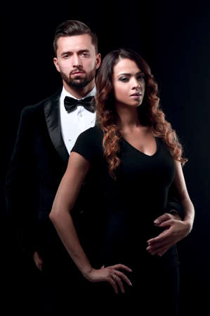 elegant man and woman posing next to each other on studio. Stock Photo