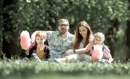 happy family sitting on the lawn in the city Park Foto de archivo - 130176450