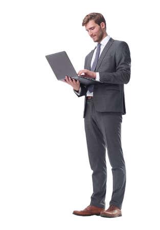 im vollen Wachstum. Geschäftsmann, der mit offenem Laptop steht Standard-Bild