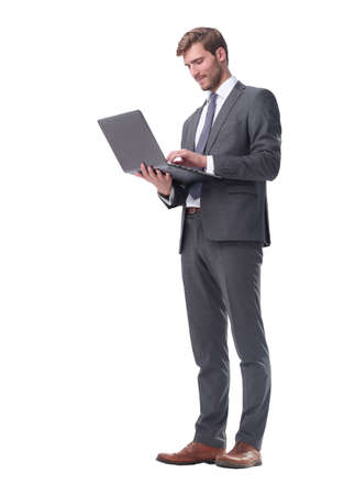 in full growth. businessman standing with open laptop Reklamní fotografie