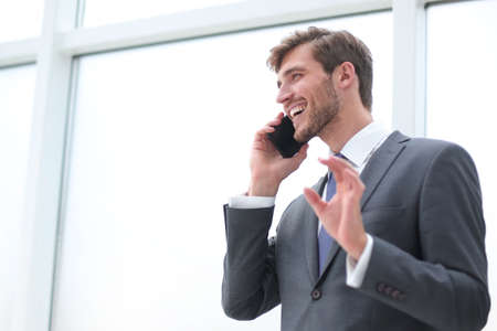 businessman talking on a mobile phone standing near the office window