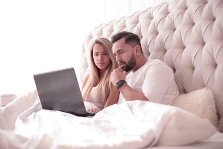 young couple browsing their favorite vidio on their laptop