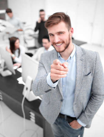 young businessman standing in the office and pointing at you