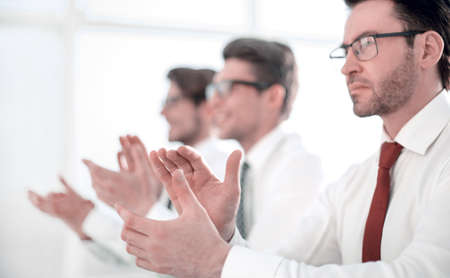 group of business people applauding sitting at the office table.