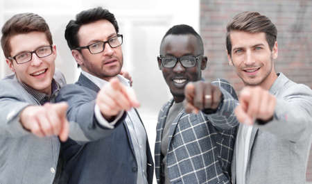 multinational business team pointing at you.