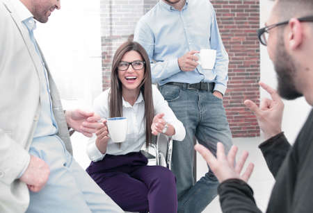 business team talking and smiling during coffee break in office