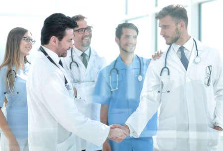 Doctores dándose la mano en el pasillo del hospital
