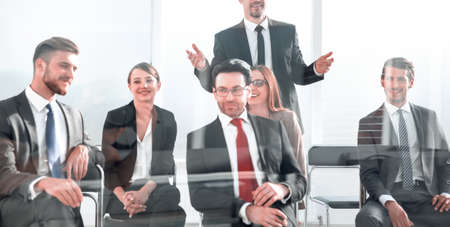 businessman standing to address colleagues at meeting