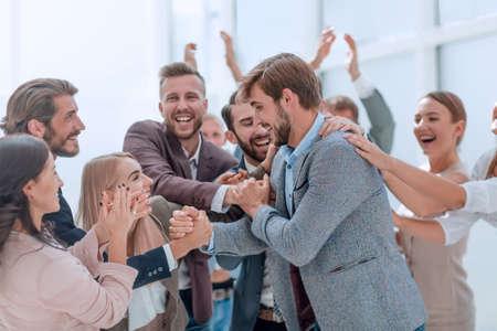 Unternehmensgruppe von Mitarbeitern, die ihren Kollegen applaudieren. Standard-Bild