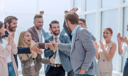 corporate group of employees congratulating their colleague.