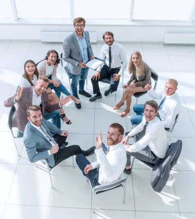 business training participants sitting in a circle and looking at the camera
