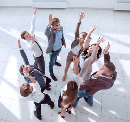 top view. successful business team standing in a circle with hands up.