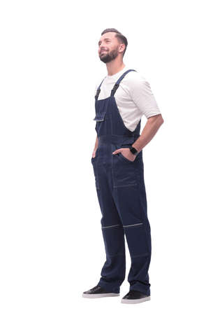 in full growth. smiling man in overalls looking at copy space Banque d'images - 130740874