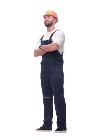 in full growth. smiling man in overalls and a safety helmet Foto de archivo - 130773715