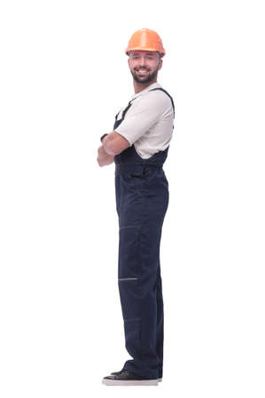 in full growth. smiling man in overalls and a safety helmet Foto de archivo - 130773734