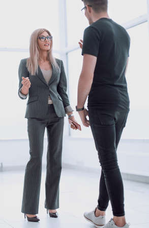 businesswoman talking to a colleague standing in the office