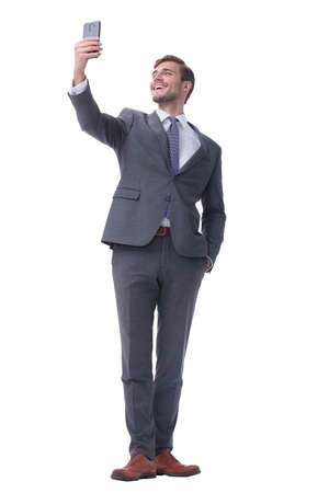 in full growth. smiling businessman taking selfie.