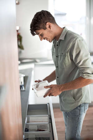 young man opens the built-in refrigerator in his kitchen.