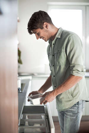 young man pulls out the food from the fridge 版權商用圖片 - 132346838