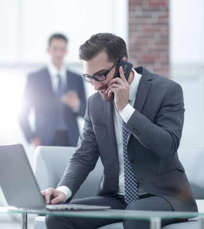 Hübscher junger Mann in Geschäftskleidung, der am Telefon spricht und lächelt, der auf dem Desktop sitzt Standard-Bild
