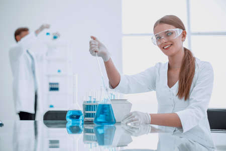 young lab technician sitting at a table in the lab.