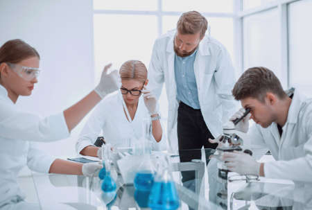 group of scientists and doctors sitting at a laboratory table