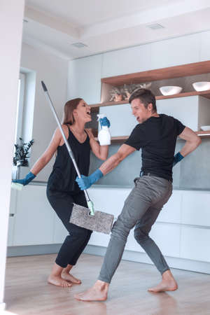 happy young couple having fun doing cleaning in their kitchen