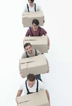 Young movers holding boxes standing in a row, isolated on white Фото со стока