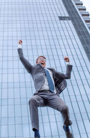 jubilant business men showing his success outdoors