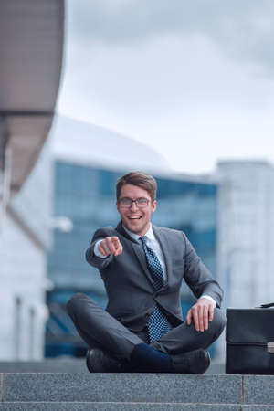 happy business man sitting on the steps and pointing at you