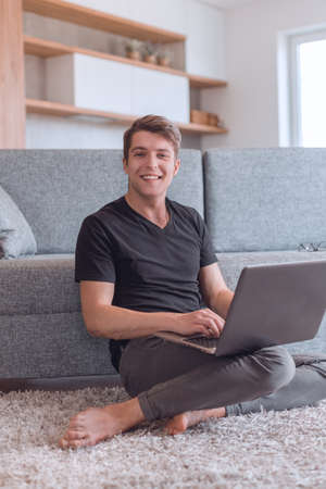 smiling young man with laptop sitting on living room floor