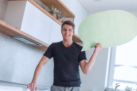 smiling man with balloon for text standing in new kitchen Reklamní fotografie
