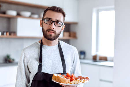 plate of sandwiches in the hands of an attractive man