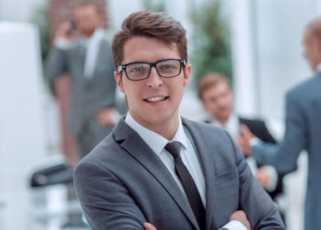 young businessman in glasses on an office background .