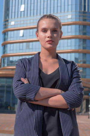 serious young woman standing in front of big office building. Фото со стока