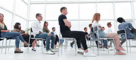 group of young people sitting in a bright conference room. Stockfoto