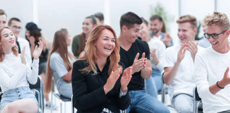 close up. smiling young woman applauding sitting in conference room