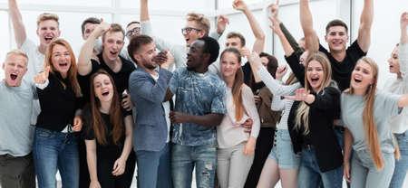 zespół szczęśliwych młodych ludzi pokazujących swój sukces