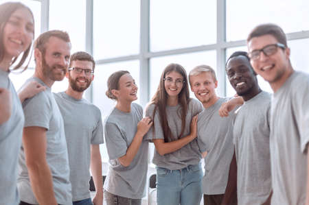 group of diverse young men in grey t-shirts standing together